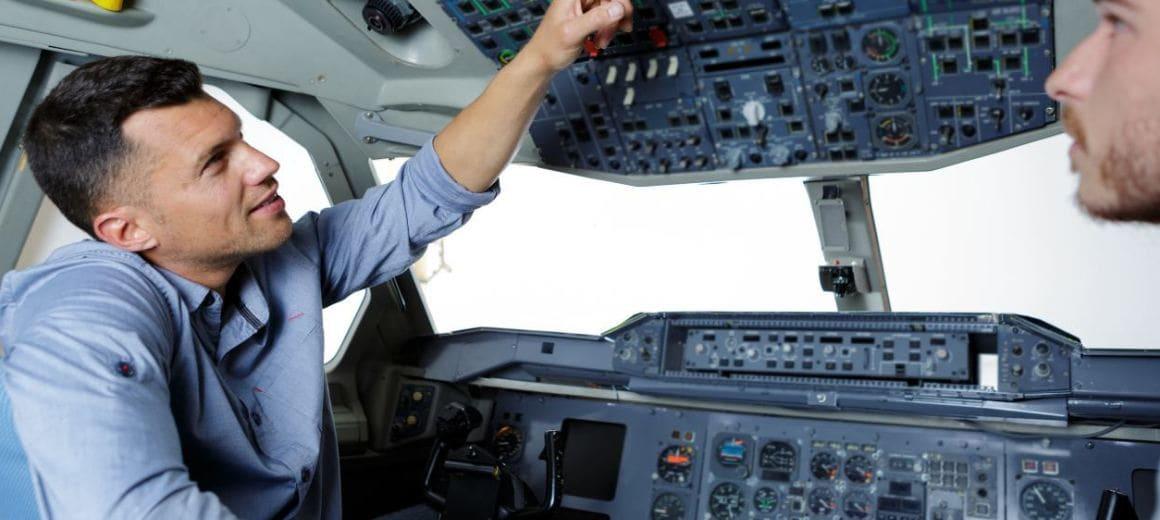 Two men in flight school in modern flight simulator for pilot training