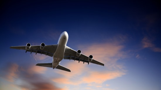 Private jet flying in a dark sky