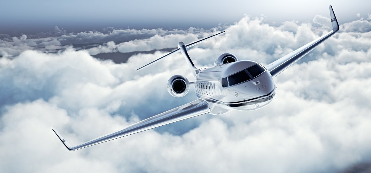 Modern private business jet flying over the clouds