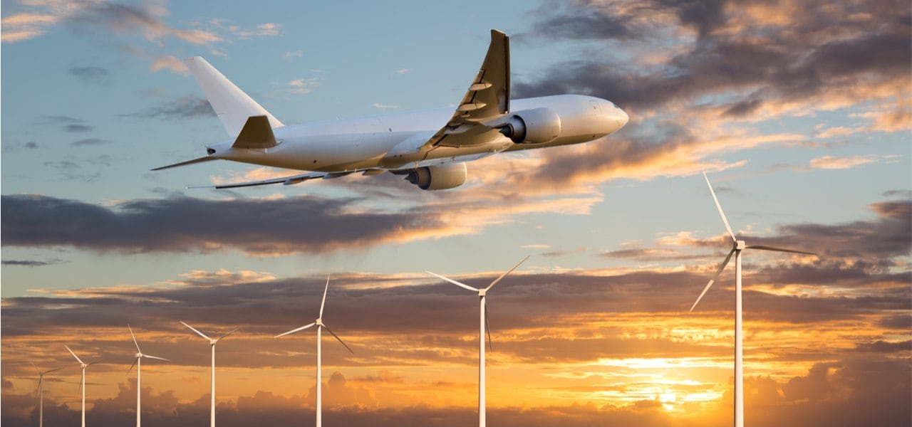 Passenger plane taking off at sunset above wind electric generators
