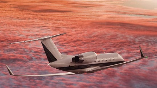 Private business jet flying in red sky