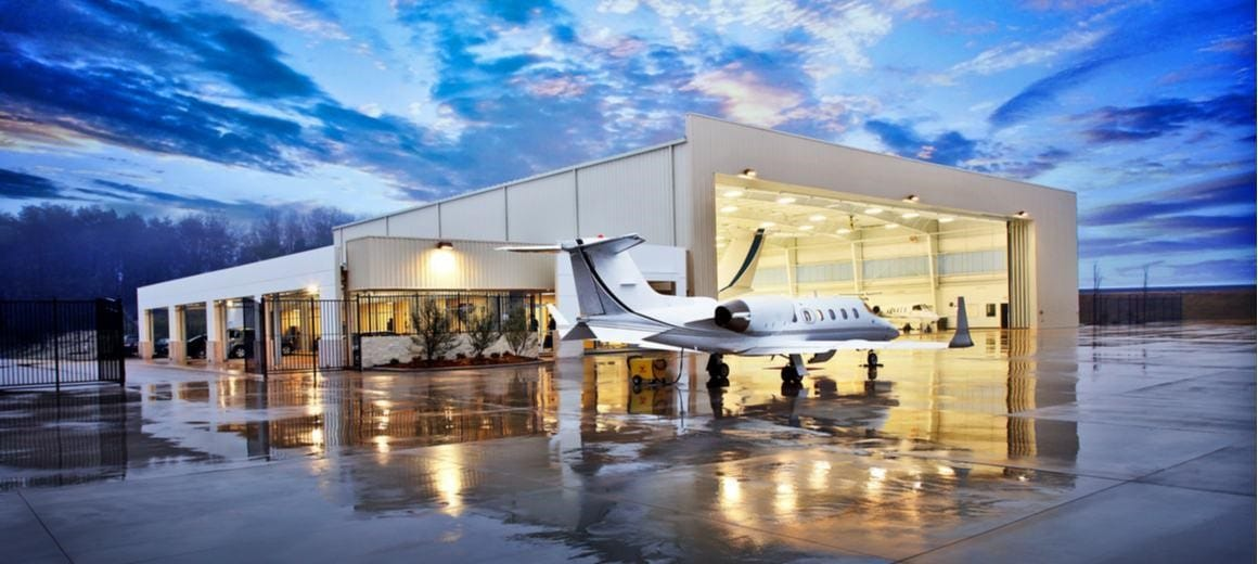 Small white private jet parked on a wet runway at night in front of airplane hangar