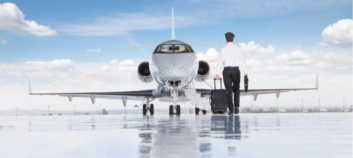 Pilot walking towards a private jet on the tarmac