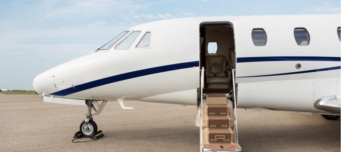 A private plane with an open door parked at a terminal