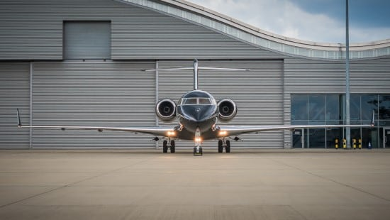 Front view of a black and silver private jet in front of an airport hangar