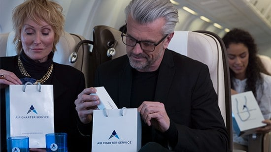 A man and a woman on a plane looking at Air Charter Service gift bags